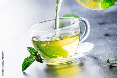 Obraz na plátně  Hot chinese green tea with mint, with splash pouring from the kettle into the cu