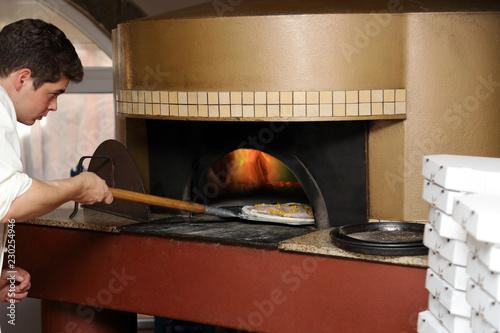 Piekarz wkłada pizzę do pieca.