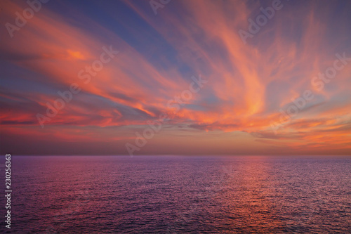 Foto  Dramatic sunset over sea surface, outdoor background