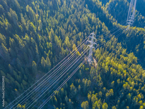 Carta da parati Aerial view of power line pylon in mountaineous area in Switzerland through vall