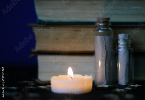 Fotografie, Obraz  Dark picture with old books, candles and spelljars