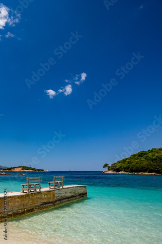Spring daytime beautiful Ionian Sea with clear turquoise water, wooden pier and fine sand coast view from Ksamil beach, Albania Canvas Print