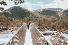 Mann Läuft Auf Einer Schmalen Brücke über Einen Reissenden Fluss In Norwegen / Man Walks On A Small Bridge Above A River In Norway