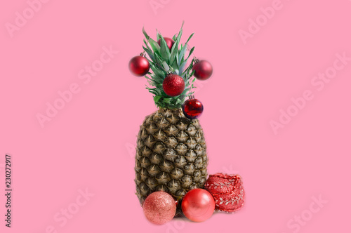 pineapple with Christmas decorations on a pink background