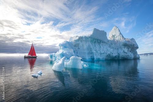 piekna-czerwona-zaglowka-na-arktyce-obok-masywnej-gory-lodowej-pokazujacej-skale-ilulissat-disko-bay-grenlandia