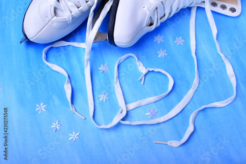 White figure skate shoelaces forming a heart against the blue background