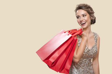 Fototapeta Portrait of happy charming woman holding red shopping bags. Yellow background.