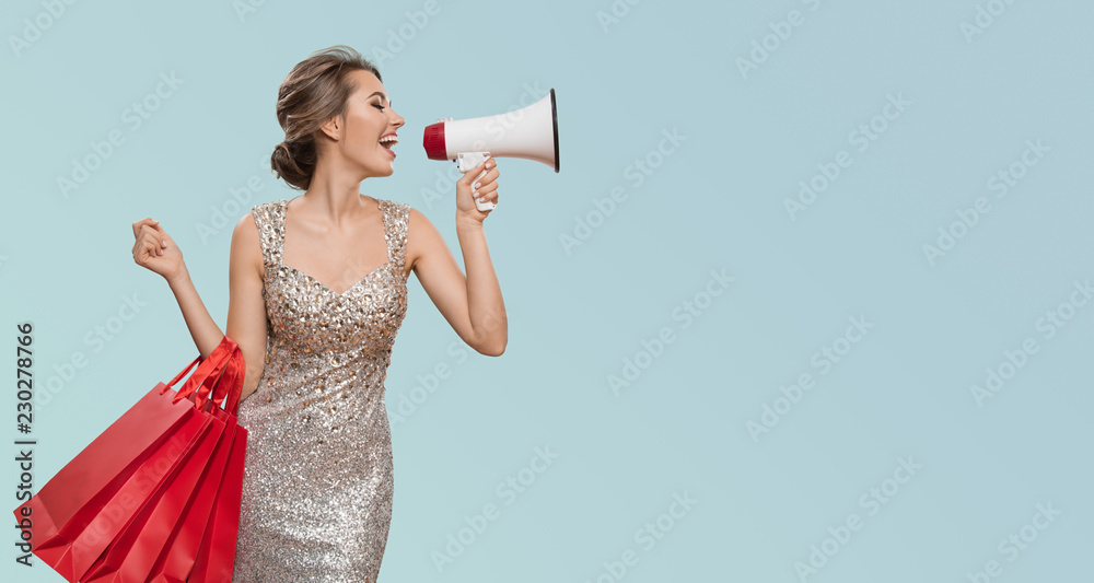 Fototapety, obrazy: Portrait of happy charming woman holding red shopping bags. Shout into megaphone on copyspace. Blue background.