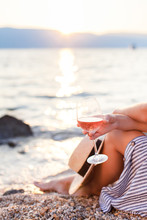 Girl Is Sitting On Sea Beach With Wineglass Of Wine At Sunset In Summer Vacation In Resort. Tourist Woman In Striped Dress With Straw Hat Is Enjoying Life, View, Relaxing, Drinking, Traveling.