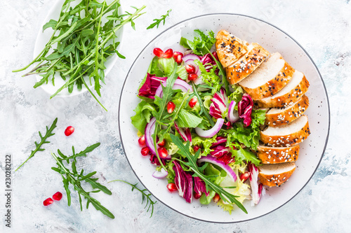 Grilled chicken breast, fillet and fresh vegetable leafy salad with arugula and pomegranate on plate