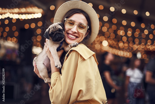 Fototapeta Lady with puppy. Cute pretty young lady wearing stylish hat and smiling while hugging adorable little puppy obraz na płótnie