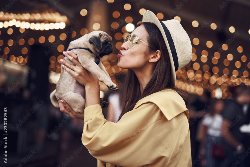 Kissing puppy. Happy young pretty lady standing outdoors with hat on her head and kissing cute puppy in her hands