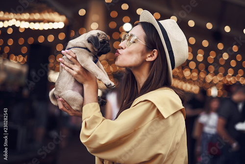 Fototapeta Kissing puppy. Happy young pretty lady standing outdoors with hat on her head and kissing cute puppy in her hands obraz na płótnie