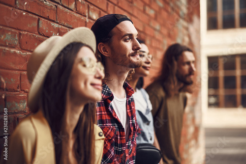 Fotografie, Tablou  Calm happy young people smiling and looking into the distance while standing aga