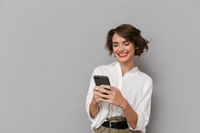Photo Of Caucasian Woman 20s Smiling And Holding Mobile Phone, Isolated Over Gray Background
