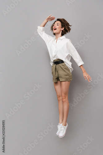 Fotografie, Tablou Full length image of caucasian woman 20s smiling and jumping, isolated over gray