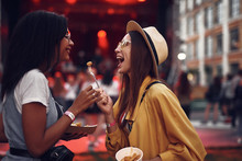 Taste This. Side View Portrait Of Lovely Girl In Hat Holding For With French Fry While Her Friend Looking At It And Smiling