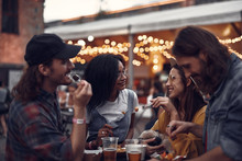 Portrait Of Young People Standing At The Table And Enjoying Meal With Drinks. Focus On Lovely Girl With Sleeping Pug Dog And Lady In Glasses