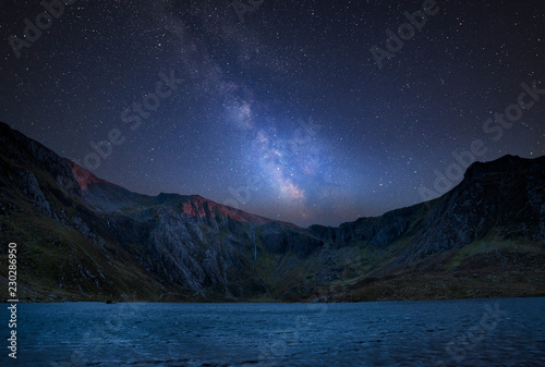 Foto auf Leinwand Blaue Nacht Digital composite Milky Way image of Beautiful landscape image of Llyn Idwal and Devil's Kitchen in Snowdoina