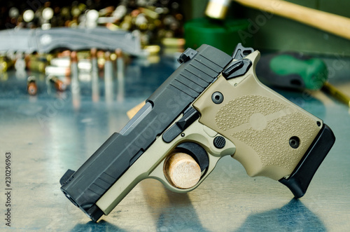 Compact 1911 9mm pistol standing on side with gunsmith tools