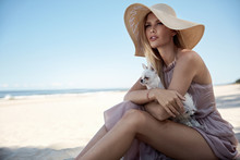 Portrait Of An Elegant Woman Relaxing On A Beach With Her Beloved Pet
