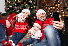 Portrait Of Happy Funny Parents And Their Two Children In Red Sweaters And Hats Making Selfie Via Mobile Phone Against Christmas Tree.