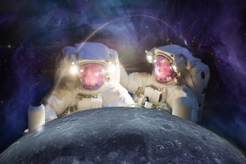 Fototapeta Two huge astronauts observe the Moon against the background of the galaxy. Elements of this image furnished by NASA