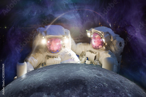 Two huge astronauts observe the Moon against the background of the galaxy. Elements of this image furnished by NASA