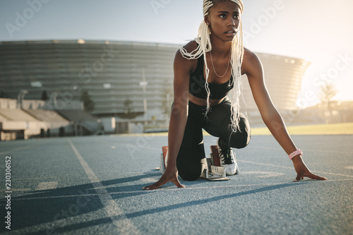 Sprinter using a starting block to start her sprint on a running Billede på lærred