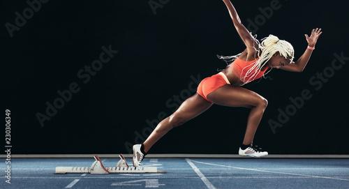 Pinturas sobre lienzo  Female sprinter taking off from starting block on a running trac