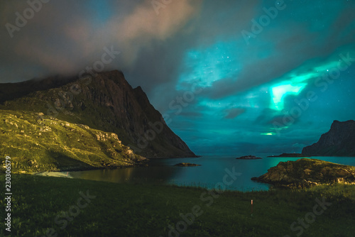 Poster Aurore polaire Aurora over sandy beach haukland, Kvalvika and Skagsanden with stones in Norway, Lofoten islands. Northern lights in Lofoten islands, Norway. Starry sky with polar lights. Night landscape with green