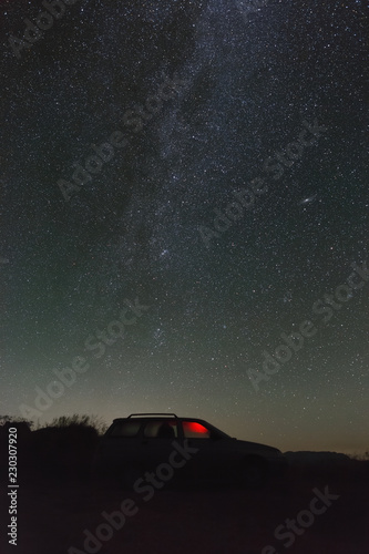 Bright stars of the Milky Way in the night sky over a parked car.