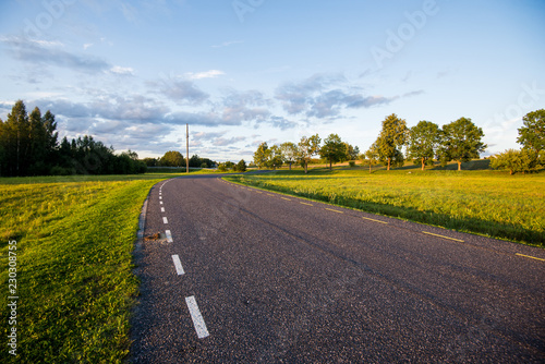 An asphalt country road through the fields with a forest in the background on a sunny day, Estonia