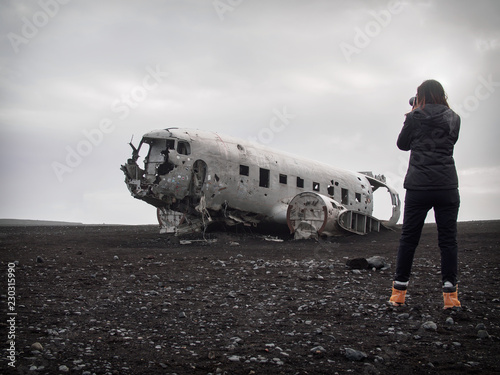 Photo  Girl is taking picture of abandoned crashed plane in Iceland in black sand deser
