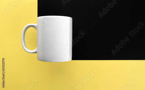 White mug on yellow and black background
