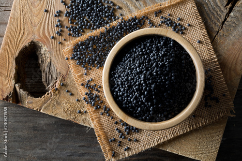 Photo Heap of black organic beluga lentils in wooden bowl from above on rustic wooden