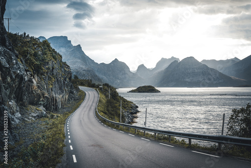 Montage in der Fensternische Dunkelgrau Winding road trip towards Henningsvaer on Lofoten Islands with mountains in the background. Cloudy and moody sky with atlantic ocean.