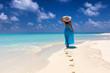 canvas print picture - Frau im blauem Kleid läuft an einem tropischen Strand und genießt ihren Urlaub