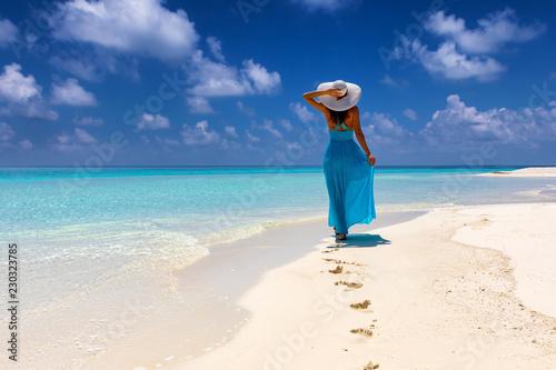 Fototapeta Frau im blauem Kleid läuft an einem tropischen Strand und genießt ihren Urlaub