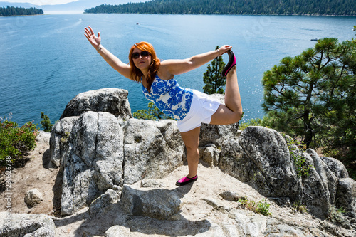 Fotografie, Obraz  Red head hair ginger woman does a yoga mediation pose on a rock on Fannette Isla