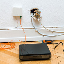 Fiber Optic Installation At Home With Obsolete CATV And New FTTH Fiber Outlets And Internet Receiver On Parquet Floor Square Image,