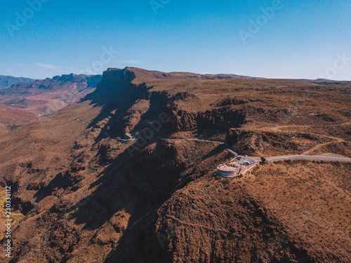 Spoed Foto op Canvas Diepbruine Aerial view of the Gran Canaria desert road through the mountains.