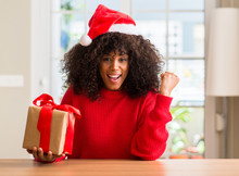 African American Woman Holding Present Wearing Christmas Red Hat Screaming Proud And Celebrating Victory And Success Very Excited, Cheering Emotion