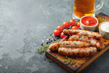 Fried Sausages With Sauces And Herbs On A Wooden Serving Board. Great Beer Snack On A Dark Background. With Copy Space