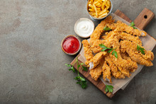Breaded Chicken Strips With Two Kinds Of Sauces And Fried Potatoes On A Wooden Board. Fast Food On Dark Brown Background. Top View With Copy Space