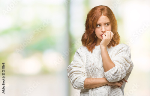 Obraz na płótnie Young beautiful woman over isolated background wearing winter sweater looking stressed and nervous with hands on mouth biting nails