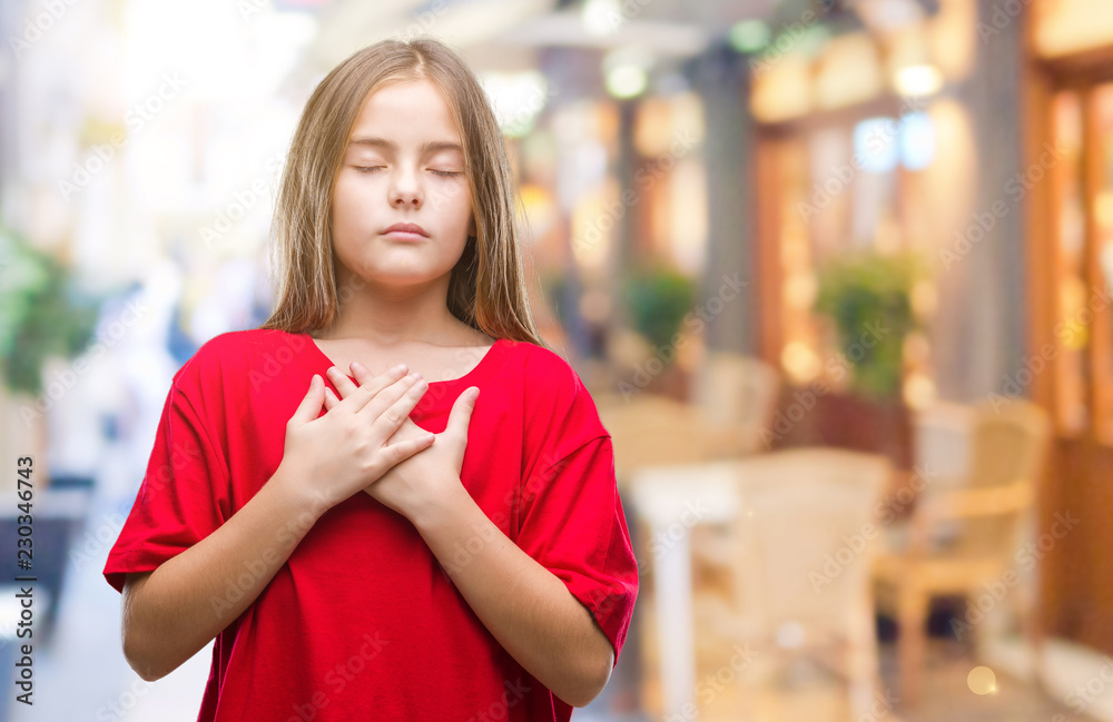 Fototapeta Young beautiful girl over isolated background smiling with hands on chest with closed eyes and grateful gesture on face. Health concept.