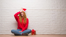 Young Redhead Woman Sitting Over Brick Wall Wearing Christmas Hat Surprised With Hand On Head For Mistake, Remember Error. Forgot, Bad Memory Concept.