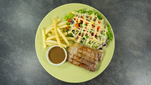 Grilled Kurobuta Pork Steak In Green Plate On A Black Rock Background. Props Decoration ,French Fries, Green Salad, Top View With Copy Space For Your Text...