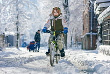 Young Boy Enjoying Cycling On Winter Sunny Day